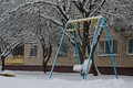 Lonely child on swing street the playground in winter under the snow in a city yard with among trees and an apartment building Royalty Free Stock Photos