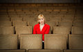 Lonely depressed woman sitting alone in empty theater sad an cinema or Stock Photography