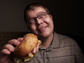 Lonely fat guy eating hamburger. Bad eating habits. Closeup. Royalty Free Stock Photo
