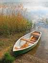 Lonely fishing boat at the lakeside in autumn Stock Photos