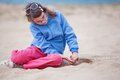 Lonely girl on beach young wearing a jumper and pink pants sits a sandy Royalty Free Stock Photography