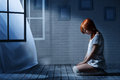 Lonely girl in a dark room sits an empty opposite the window Royalty Free Stock Photo