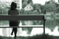 Lonely girl by the lake young lost in memories is sitting on a bench next to a calm Stock Images