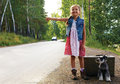 Lonely girl standing on the road with a suitcase and a dog, rais Royalty Free Stock Photo