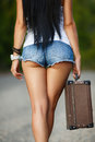 Lonely Girl with a suitcase on a country road ... Royalty Free Stock Photo