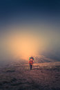 Lonely hiker  with backpack walking along the trail on the mountain top at foggy day time. Royalty Free Stock Photo