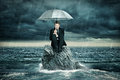 Lonely island man with umbrella sitting on Stock Images