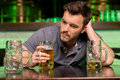 Lonely man in bar depressed young drinking beer and holding hand hair while sitting Stock Images