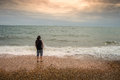 Lonely man at the beach standing sunset looking into distance Royalty Free Stock Photos