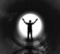 Lonely man at the end of dark tunnel a person is a with a bright white light shining has his hands in air for a religious or Royalty Free Stock Image