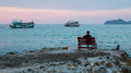 Lonely man sits on a bench on the coast watching the fishing boats Royalty Free Stock Photo