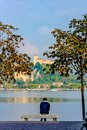 Lonely man sitting between two trees on a bench and looking at the lake. In the distance you can see the island on which stands th Royalty Free Stock Photo