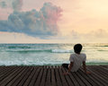 Lonely Man sitting in wooden dock pier in sea beach with twilight sky in sunset time and think concentrate Royalty Free Stock Photo