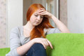 Lonely teen girl sits on sofa at home Royalty Free Stock Images