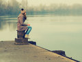 Lonely teenage girl sitting on the dock cold winter day Stock Photography