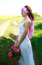 Lonely thoughtfully girl with basket flowers in a field poses on the background of country road Stock Photo