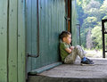 Lonely and upset kid sad boy sitting on an old train platform Stock Photo