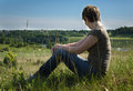 Lonely woman sitting with her back on green field Royalty Free Stock Photo