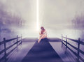Lonely woman sitting on pier with ball of glowing light in her hand Royalty Free Stock Photo