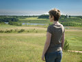 Lonely woman standing with her back on green field Royalty Free Stock Photo
