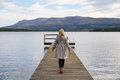 Lonely woman walking on a pier with lake and mountains in the background Stock Photos