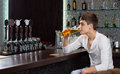 Lonely young man drinking alone at the pub sitting end of bar counter sipping a pint of draught beer Stock Photography