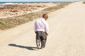 Lonesome walking dwarfish african man down a dirt road along the coast with his head bent down Royalty Free Stock Images