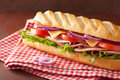 Long baguette sandwich with ham cheese tomato lettuce Royalty Free Stock Photo