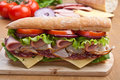 Long baguette sandwich with meat and vegetables Royalty Free Stock Photo