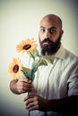 Long beard and mustache man giving flowers on gray background Royalty Free Stock Photo