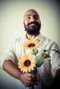 Long beard and mustache man giving flowers on gray background Stock Photography