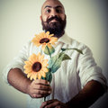 Long beard and mustache man giving flowers on gray background Stock Photo