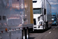 Long big rigs semi trucks and trailer convoy on the road Royalty Free Stock Photo