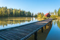 Long bridge going to the house on a small island located forest lake Royalty Free Stock Images