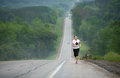 Long distance runner a on a remote desert highway Stock Photography