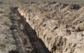 Long earthen trench dug to lay pipe the in the earth in the desert Royalty Free Stock Photo