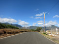 Long empty road in maili valley next to naval magazine and mountains the distance on oahu hawaii Royalty Free Stock Image