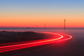 Long exposure red car light trails on a road outside at foggy night on blue hour with electrical power lines and pylons disappear Royalty Free Stock Photo
