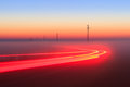 Long exposure red car light trails on a road outside at foggy night on blue hour with electrical power lines and pylons disappear Royalty Free Stock Image