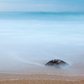 Long exposure rock on the beach photo of a a buried in sand and covered by ocean copy space Royalty Free Stock Photography
