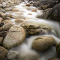 Long exposure stream over rocks to beach water worn ancient detail on secluded Stock Photo