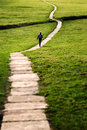 Long flagstone path through field woman walking on a pathway snaking a grassy in the yorkshire dales england uk focus vignette Stock Image