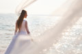 Long flying veil young bride is standing near sparkling water with selective focus Stock Photo
