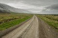 Long gravel road straight across icelandic meadows with misty mountains in the background Stock Photography