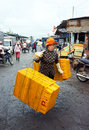Long hai viet nam july the women with tired face rattan plastic tray into market she wear yellow hat step on marshy Royalty Free Stock Images
