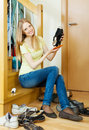 Long haired blonde woman cleaning shoes at home Stock Photography