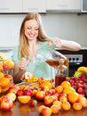 Long haired girl cooking fresh beverages positive blonde with fruits Stock Photos