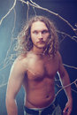 Long haired naked man in the forest Stock Photos