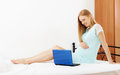 Long haired pregnancy woman with laptop in her bed at home Royalty Free Stock Photo
