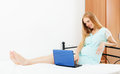 Long haired pregnant woman with laptop in bed at home Royalty Free Stock Photos